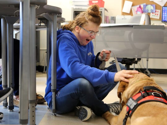 After finishing her assignment, Jolie Regan, 15, pets