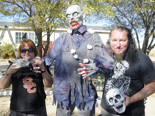 Lynn Pennington and her son, Keith Webb, stand with their newest Halloween addition, Oscar the zombie.