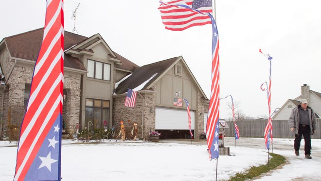 Terry Adams walks to the barn at his Brighton Township home, which reflects his and his wife's strong sense of patriotism.