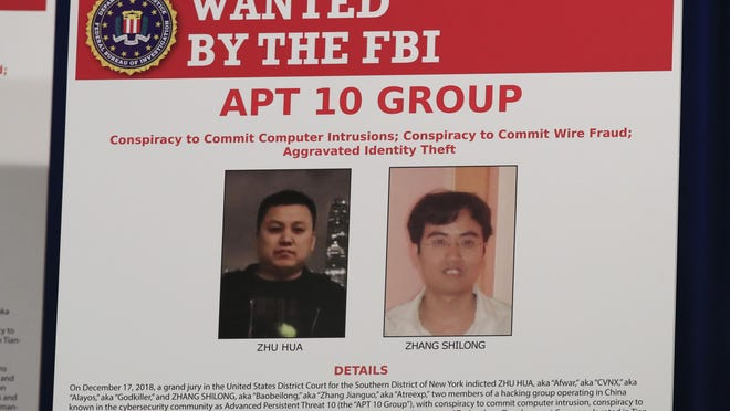 A poster displayed during a news conference at the Department of Justice in Washington, Dec. 20, 2018, shows two Chinese citizens suspected to be with the group AP 10 carrying out an extensive hacking campaign to steal data from U.S. companies.