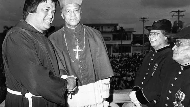 In this undated file photo, then-Father Anthony Apuron, left, shakes hands with Bishop Felixberto Flores.