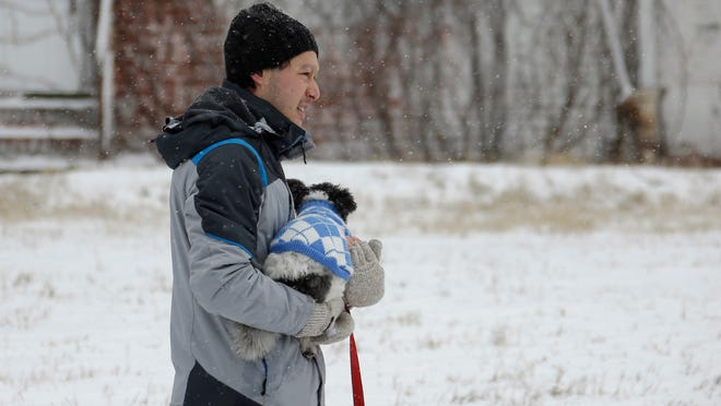 A man takes his dog for a walk in this weekend's snow. Although it may not apply in this case, veterinarians advise wiping a dog's paws after a walk on streets and walkways that have been treated with de-icers such as salt. The chemicals can irritate the dog's paws.