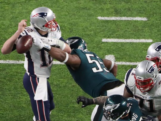 New England Patriots quarterback Tom Brady (12) fumbles the ball as he is hit by Philadelphia Eagles defensive end Brandon Graham (55) during the fourth quarter in Super Bowl LII at U.S. Bank Stadium.