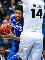 University of Memphis forward Dedric Lawson (left) drives to the basket against Central Florida University defender Nick Banyard during second-half action. Lawson scored a team-high 12 points off  3 of 14 shooting.