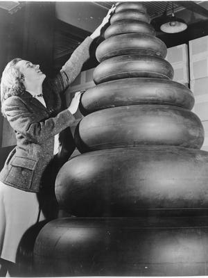 Woman standing next to a wide range of tire sizes required by military aircraft, 1941.