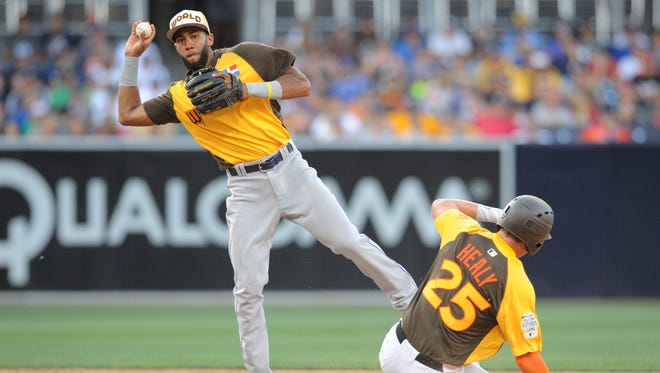 World infielder Amed Rosario (left) throws to first base as USA runner Ryon Healy slides during the All Star Game futures baseball game at PetCo Park in San Diego on  Jul 10, 2016.