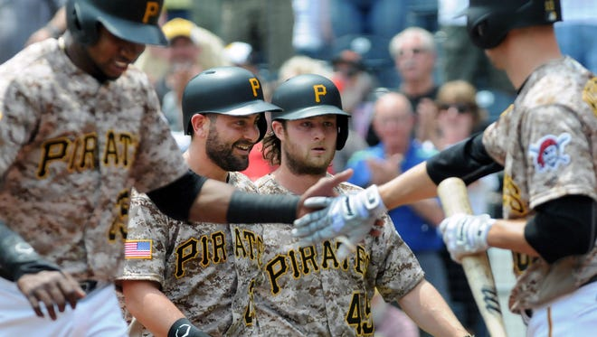 Pittsburgh Pirates' Gregory Polanco, left, shakes hands with Jordy Mercer, right, as catcher, Francisco Cervelli, walks with pitcher, Gerrit Cole, (45) after Cole hit a three-run home run in the second inning of a baseball game against the Arizona Diamondbacks, Thursday, May 26, 2016 in Pittsburgh. The Pirates won 8-3.