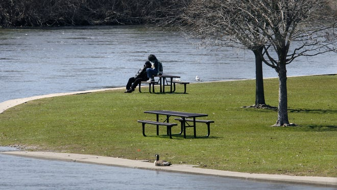 Elkhart residents enjoy a nice afternoon in McNaughton Park next to the St. Joseph River in Elkhart on Wednesday, April 8, 2009. A lot of people in the town have time on their hands, with the city facing a skyrocketing unemployment rate. (Charlie Nye / The Star).