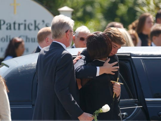 William Dym, 20, is hugged after a funeral Mass for