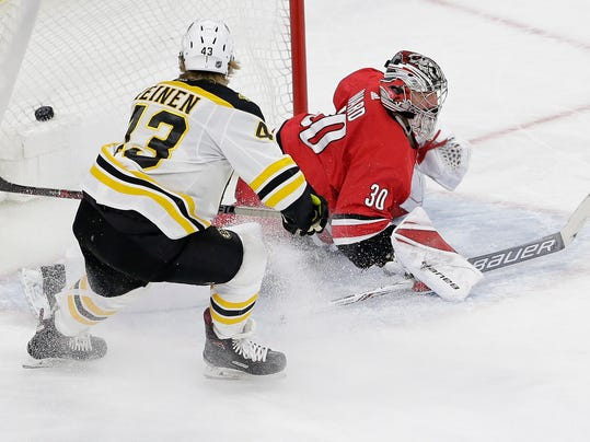 Boston Bruins' Danton Heinen (43) scores against Carolina Hurricanes goalie Cam Ward (30) during the third period of an NHL hockey game in Raleigh, N.C., Tuesday, March 13, 2018. Boston won 6-4. (AP Photo/Gerry Broome)