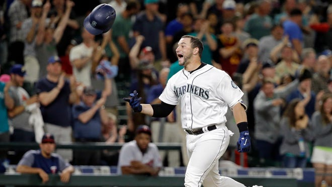 Seattle Mariners' Mike Zunino tosses his batting helmet as he heads home on his two-run home run, scoring the winning run against the Minnesota Twins in the ninth inning of Wednesday's game.