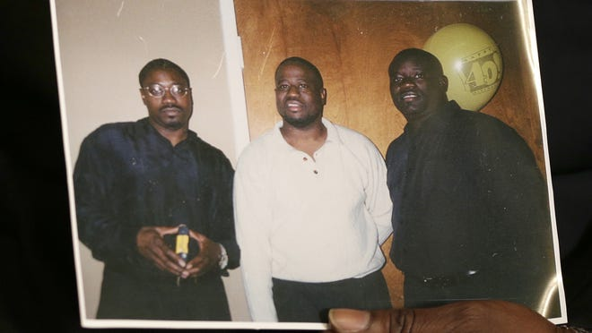 In this April 8, 2015 photo, Anthony Scott holds an undated photo that shows himself, center, and his brothers Walter Scott, left, and Rodney Scott, right, as he talks about Walter at his home near North Charleston, S.C. Walter Scott was killed by a North Charleston police officer after a traffic stop on Saturday, April 4, 2015. The officer, Michael Thomas Slager, has been fired and charged with murder.