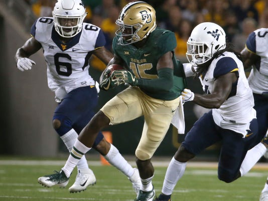 Baylor wide receiver Denzel Mims (15) runs past West Virginia safety Dravon Askew-Henry (6) and West Virginia cornerback Mike Daniels Jr. (4) in the first half of an NCAA college football game, Saturday, Oct. 21, 2017, in Waco, Texas. (AP Photo/Jerry Larson)