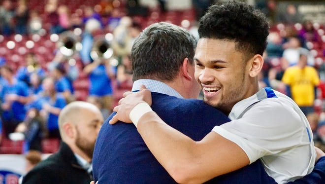 Olympic's Jaiden Mosley gets a hug from coach Devin Huff after the Trojans defeated Prosser 59-54 in overtime Thursday in the quarterfinals of the Class 2A state boys basketball tournament at the Yakima Valley SunDome.
