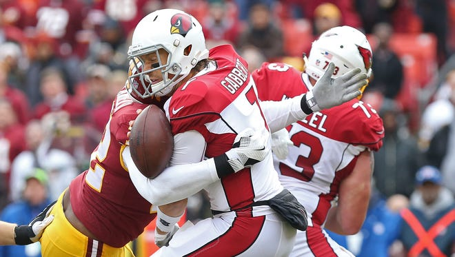 Arizona Cardinals quarterback Blaine Gabbert (7) fumbles the ball while being hit by Washington Redskins defensive lineman Anthony Lanier II (72) in the first quarter at FedEx Field.
