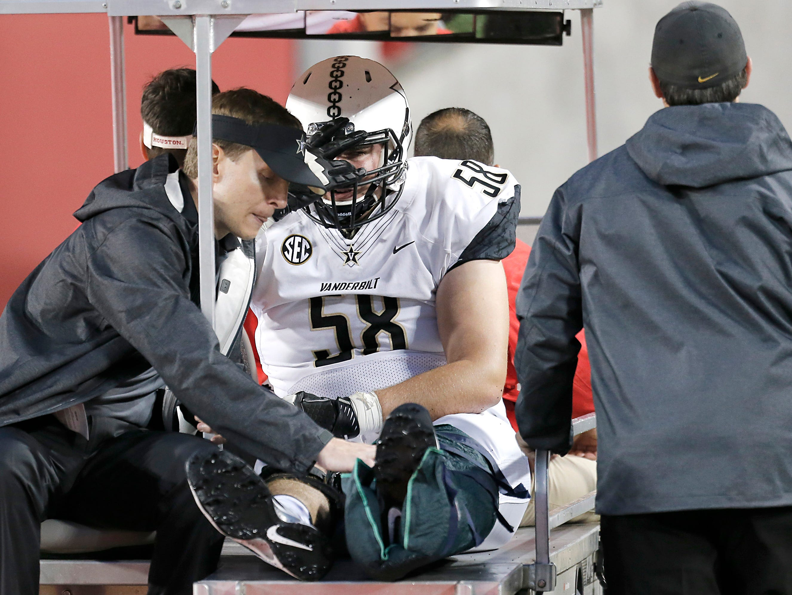 Injured Vanderbilt offensive lineman Justin Skule (58) leaves the field after getting hurt playing against Houston in the first quarter on Oct. 31, 2015.