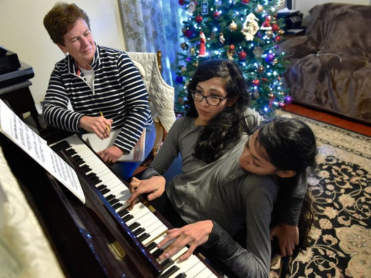 Piano teacher Cindy Iffland listens as conjoined twins Carmen and Lupita Andrade play the piano during a lesson at their home on Dec. 14, 2016. Carmen and Lupita play using Carmen's right hand and Lupita's left. They have been taking lessons, at their mother's insistence, for about eight years.