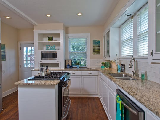 The hardwood floors extend into the kitchen which features generous granite counter space with a white subway tile back splash, glass cabinet doors and a gas stove on the island.
