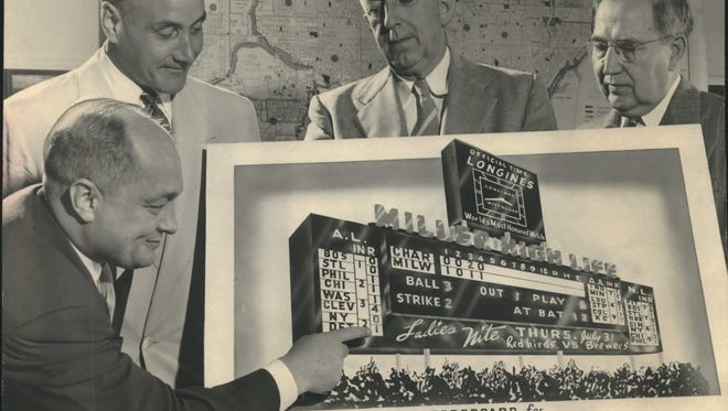 """Frederick C. Miller (top left), president of Miller Brewing Co., beams as County Stadium manager Fredric (Shorty) Mendelson shows off a drawing for the new scoreboard for Milwaukee County Stadium at the Milwaukee County Courthouse on Aug. 1, 1952. Miller Brewing """"donated"""" the $75,000 scoreboard in return for advertising rights. Also looking on: Eugene A. Howard (center), the county's director of public works; and Jerome C. Dretzka, executive secretary of the County Park Commission. This photo was published in the Aug. 2, 1952, Milwaukee Journal."""