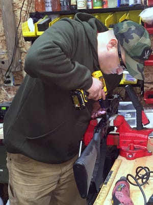 Gunsmith Kevin Rogers installs a bullet guide in a Saiga rifle in his Millerton shop.