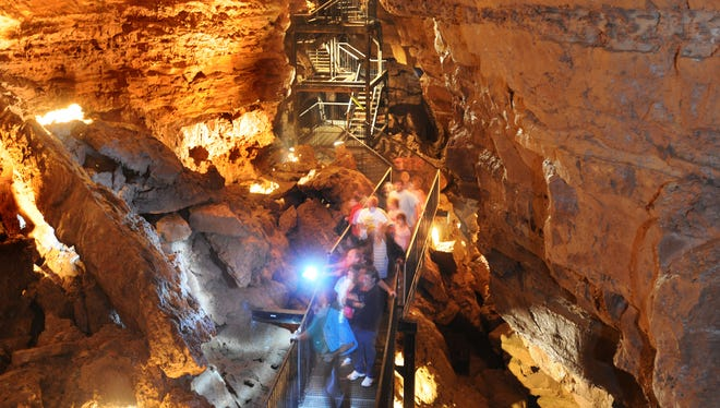 A tour group moves across a metal walkway between the towering walls of Indiana Caverns in Corydon, Ind.