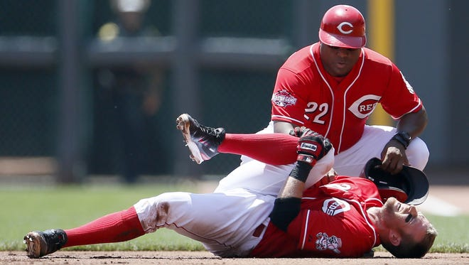 Zack Cozart clutches his knee as first base coach Billy Hatcher offers support after the Reds' shortstop tumbled while being thrown out at first base during the bottom of the first inning Wednesday against the Phillies.