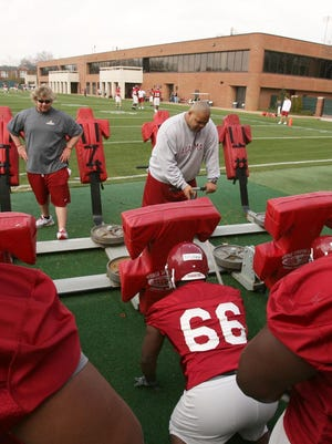 Alabama defensive line coach Bo Davis adjusts the blocking sled as players prepare to work on blocking skills during football practice in 2008.