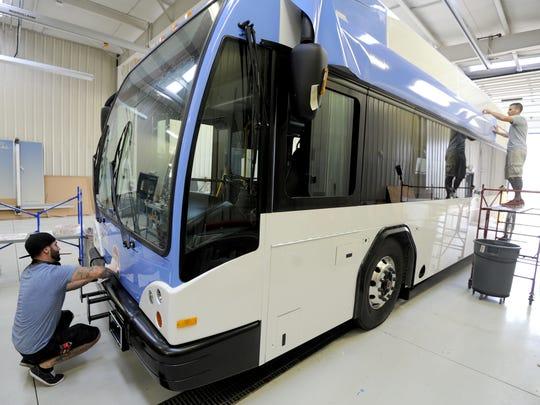 Installers place decals on a new RTA bus destined for Cleveland's transit system.