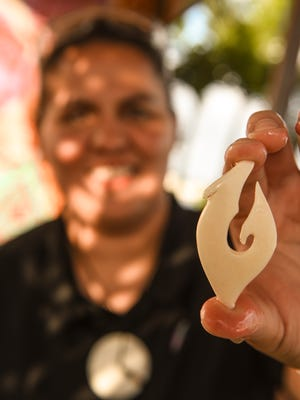"Carving apprentice Alea Dugan displays her Chamoru bone haguet, or fish hook, she was shaping at the Sågan Kotturan Chamoru Cultural Center on Wednesday, Mar. 7, 2018. Dugan is studying the art of Chamoru jewelry making under traditional and contemporary Chamorro body ornamentation artist, Julie ""Jill"" Quichocho Benavente, at the center."