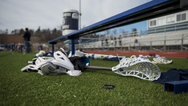 Lacrosse sticks sit on the sidelines during a boys high school lacrosse game.