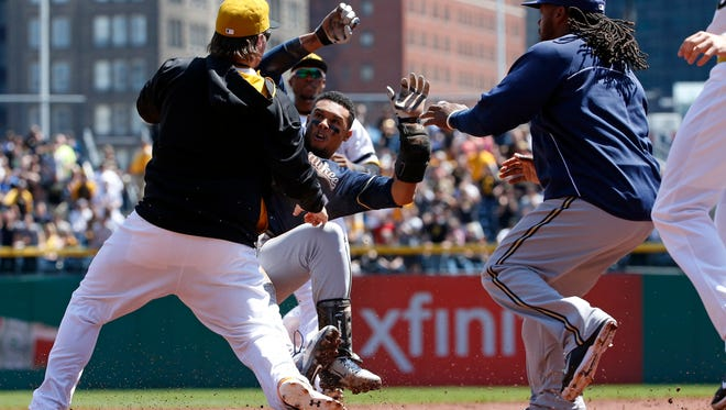 The Pirates' Travis Snider, left, takes down the Brewers' Carlos Gomez as the Brewers' Rickie Weeks, right, joins a skirmish between the two teams during the third inning Sunday in Pittsburgh.
