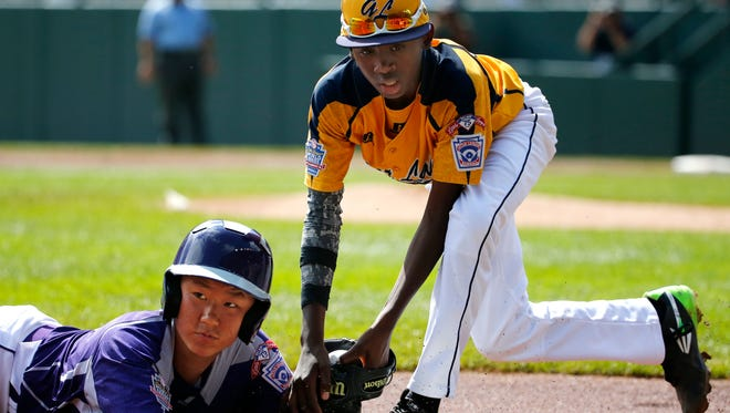 South Korea's Jae Yeong Hwang, left, is tagged out by Chicago's Cameron Bufford while attempting to steal third in the first inning of the Little League World Series championship baseball game in South Williamsport, Pa., Sunday, Aug. 24, 2014. (AP Photo/Gene J. Puskar