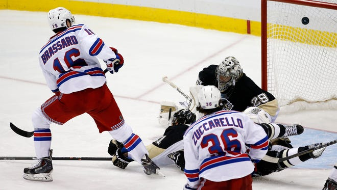 The Rangers' Derick Brassard (16) puts the puck past Penguins goalie Marc-Andre Fleury for the game-winning goal in overtime Friday night.