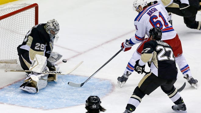 Penguins goalie Marc-Andre Fleury (29) stops a shot by Rangers forward Rick Nash (61) in the first period of Game 2 in Pittsburgh on Sunday night.
