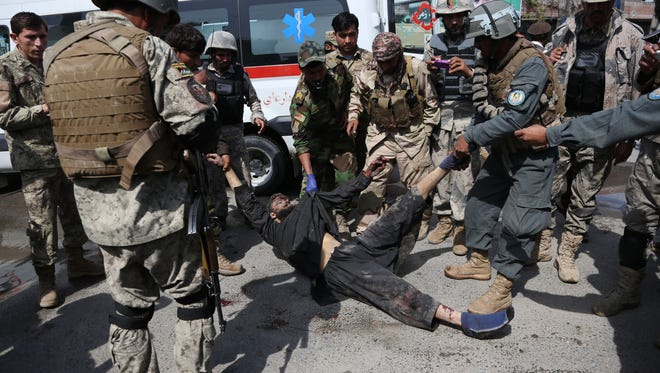 Afghan army and police officers move the body of an insurgent from the scene after the Taliban staged an attack on a police station in Jalalabad, eastern Afghanistan, on Thursday.