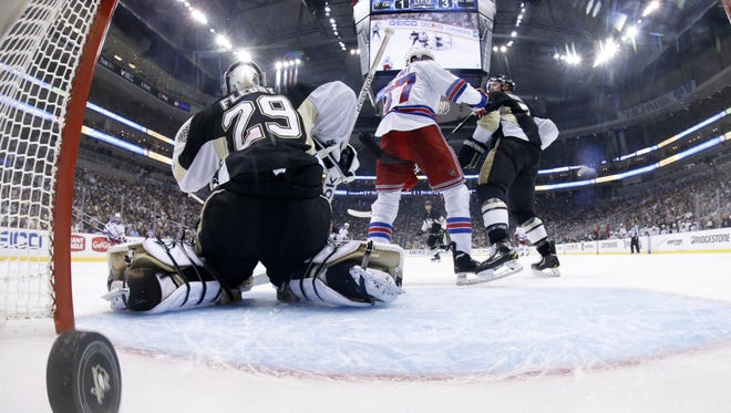 In this photo taken with a fisheye lens, a goal by the Rangers' Ryan McDonagh gets past Pittsburgh Penguins goalie Marc-Andre Fleury (29) in the second period of Game 5  Friday night. The Rangers won 5-1.