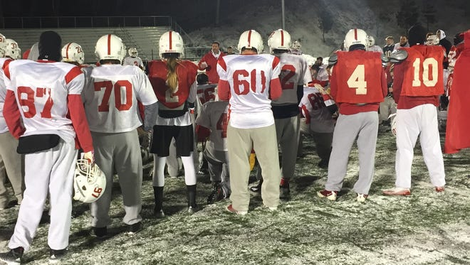 Members of the St. John's football team gather around MIAC coach of the year Gary Fasching following practice Tuesday night at Clemens Stadium.