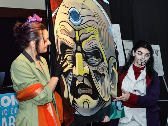 """Cosplayers Jo Roberts, left, and Anna Faulkner present a painting of """"Doctor Who"""" villain Davros by Gabriel Smith during the live auction at Pensacon's inaugural """"Dress Up or Dress Up Costume Ball"""" at Pensacola Little Theatre. The event returns Saturday."""