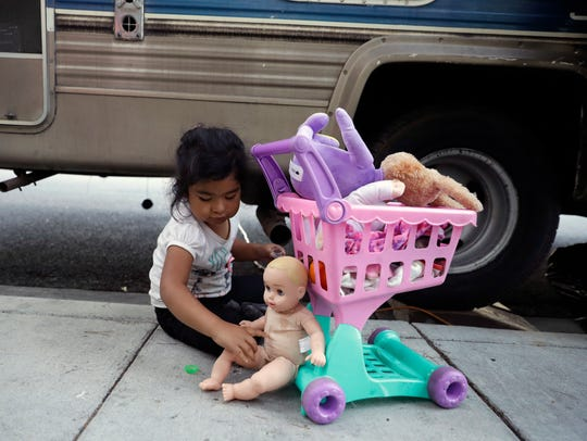 Delmi Ruiz Hernandez, 4, top, plays outside of an RV