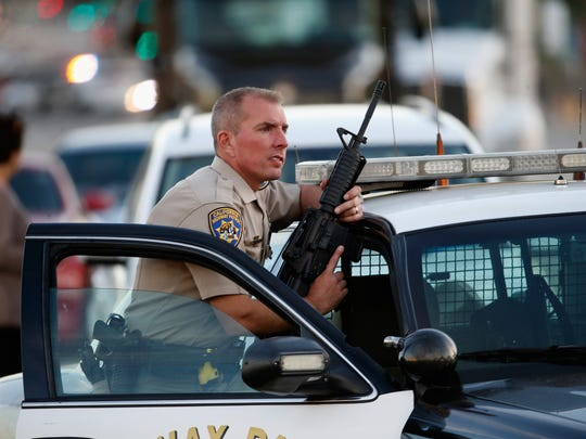 Officer Dane Norem officer stands with his weapon during the San Bernardino terror attacks on December 2, 2015