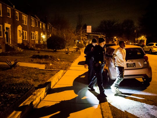 Wilmington Police Department officers lead a stabbing suspect to their patrol car on Sunday night, Dec. 18, 2016.