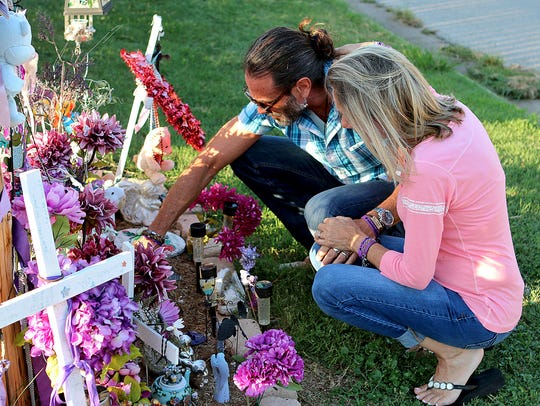 Vern and Bianka Landavazo look over mementos left behind at the memorial for their daughter, Lauren Landavazo, on Aug. 28, 2017. Lauren was murdered on Sept. 2, 2016