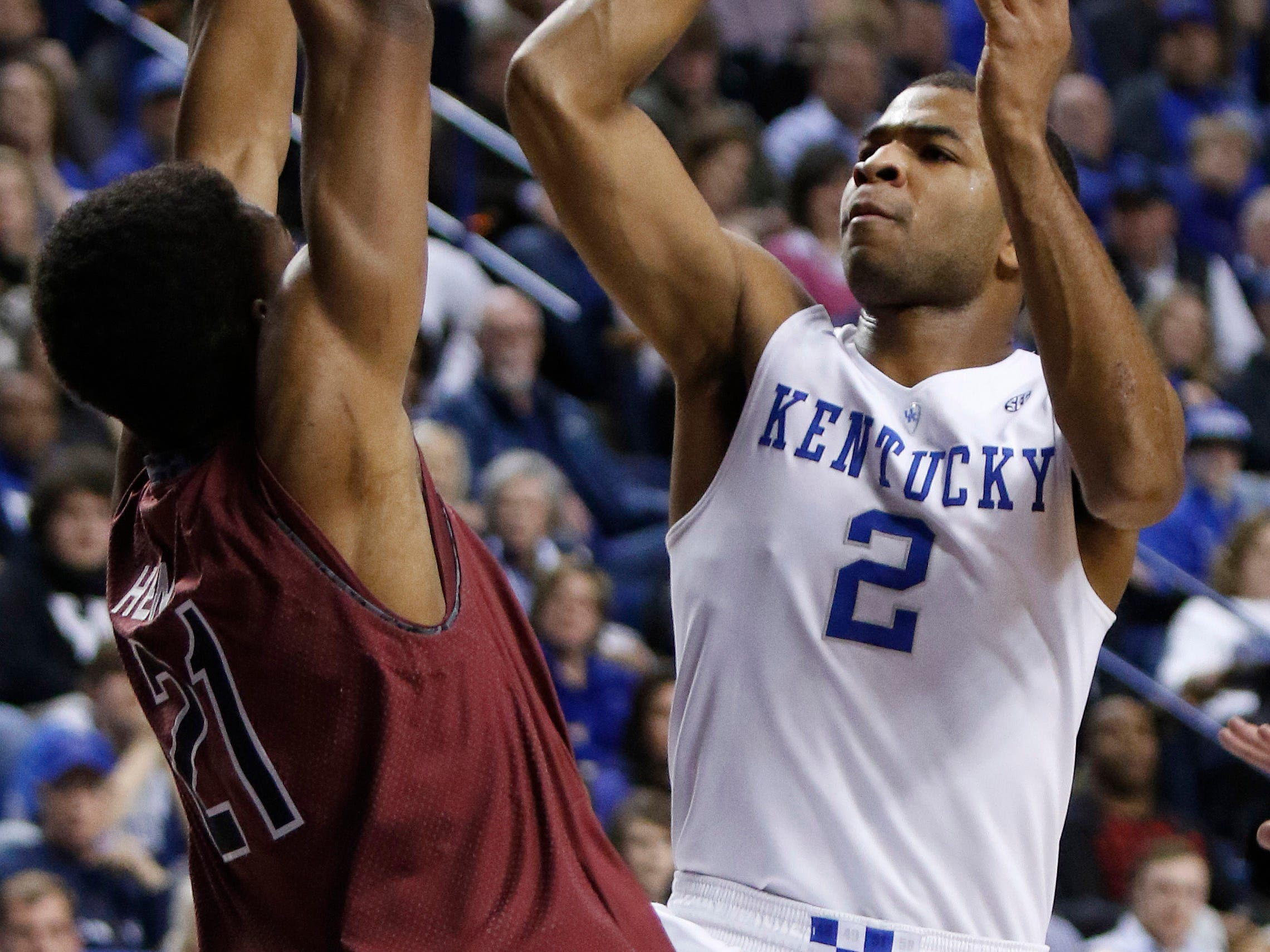 Kentucky's Aaron Harrison (2) shoots while defended by South Carolina's Demetrius Henry during the first half of an NCAA college basketball game, Saturday, Feb. 14, 2015, in Lexington, Ky. (AP Photo/James Crisp)