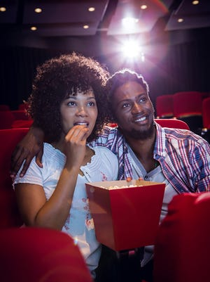 A young couple watching a movie at the cinema.