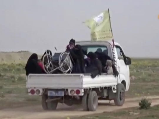 In this Feb. 10, 2019 image from video provided by Hawar News Agency, ANHA, an online Kurdish news service, civilians flee fighting near Baghouz, Syria. Fierce fighting was underway Monday between U.S.-backed Syrian forces and the Islamic State group around the extremists' last foothold in eastern Syria.