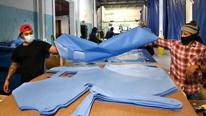 Ken Goncalves, right, and John Paulo take pieces of vinyl acetate out of a die-cutter while making medical gowns at Contollo Mass Manufacturing in Franklin Wednesday. The gowns are for non-surgical use and will go to hospitals and first responders.