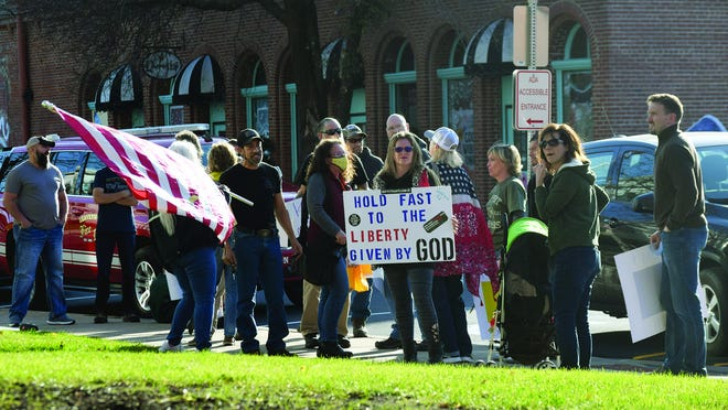 People gather outside of Leavenworth City Hall on Thursday in protest of a city mask mandate. They gathered as city commissioners met to discuss the mask mandate, which was approved.