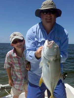 Camron Jordan smiled approvingly at the crevalle jack Jim Jordan subdued at rocks off Bonita Beach, where they also caught and released several snook with Get Hooked Charters Capt. Matt DeAngelis.