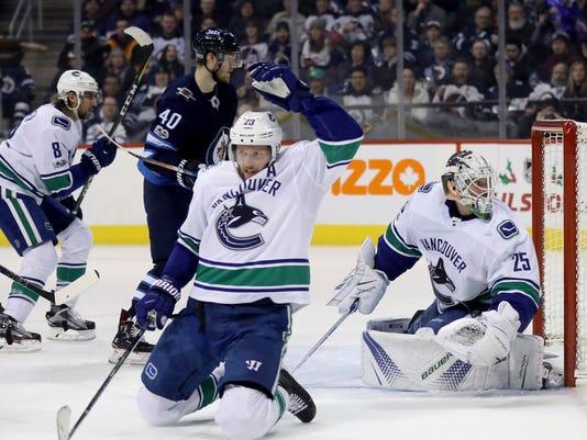 A shot by Winnipeg Jets' Nikolaj Ehlers (not shown) beats Vancouver Canucks' Alexander Edler (23) and goalie Jacob Markstrom (25) during second-period NHL hockey game action in Winnipeg, Manitoba, Monday, Dec. 11, 2017. (Trevor Hagan/The Canadian Press via AP)