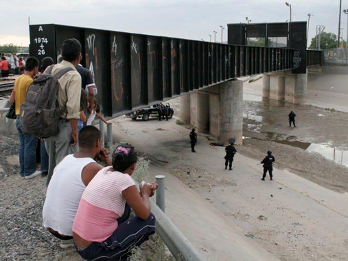 People gather at the spot near the Paso del Norte Bridge,